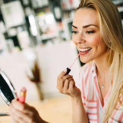 bigstock-Young-Beautiful-Woman-Applying-240949429
